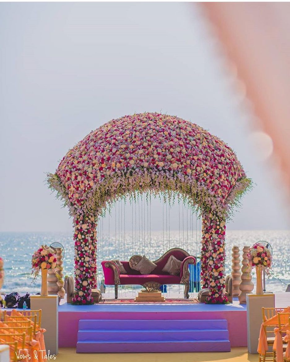 purple violet and pastel yellow flower decoration mandap in dome shape for beach wedding decor with purple and golden mandap sofa chair