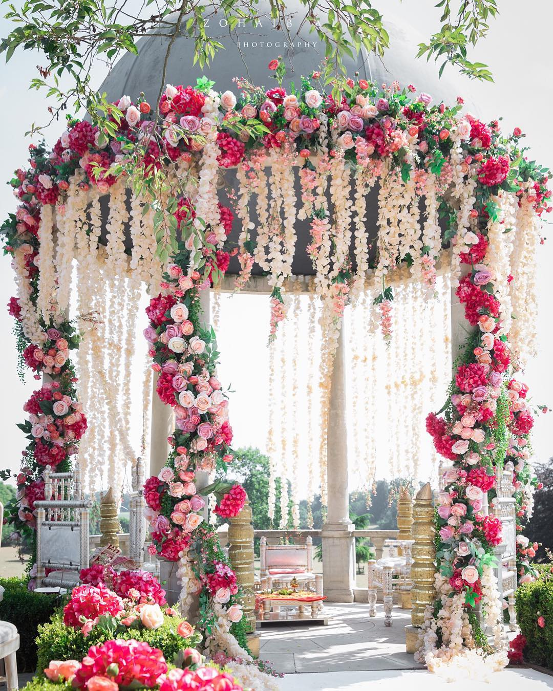 Wedding mandap decoration with flowers in shades of pink and white - using an existing dome structure at the venue