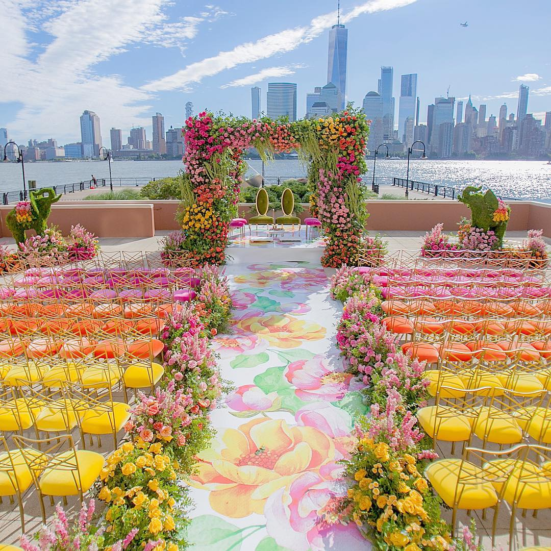 floral mandap decoration with floral aisle and with pink, yellow and orange colour chairs for guests seating -  plus olive & golden wedding mandap chairs