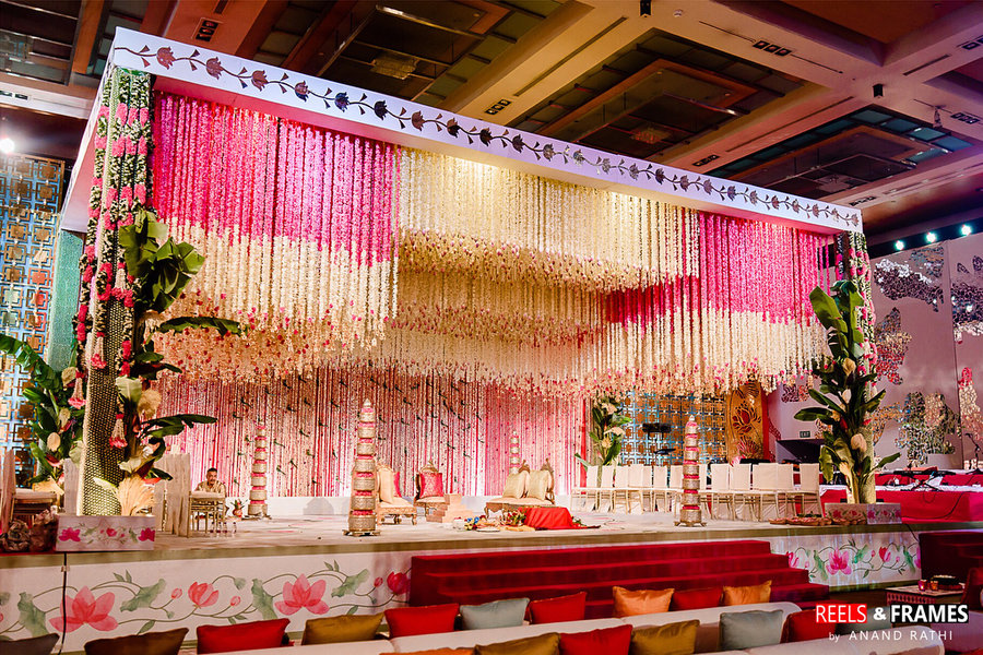 wedding mandap decoration with white, cream and pink flower cieling and banana leaves on the corners