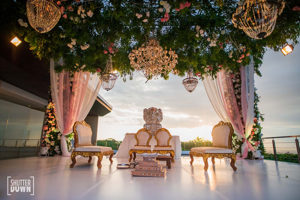 rooftop mandap with floral decoration plus cream and golden wedding mandap chairs