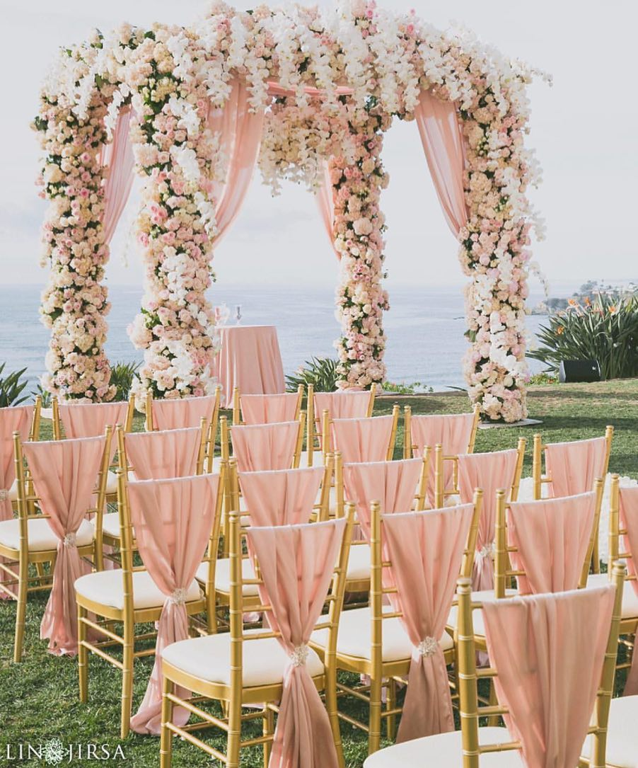 beach wedding dome shaped mandap decorated with pink and white flowers plus with pink and golden chairs for guests seating