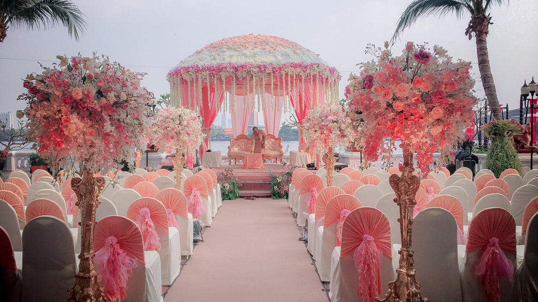 dome shape floral wedding mandap with pink and white colour chairs for guest seating