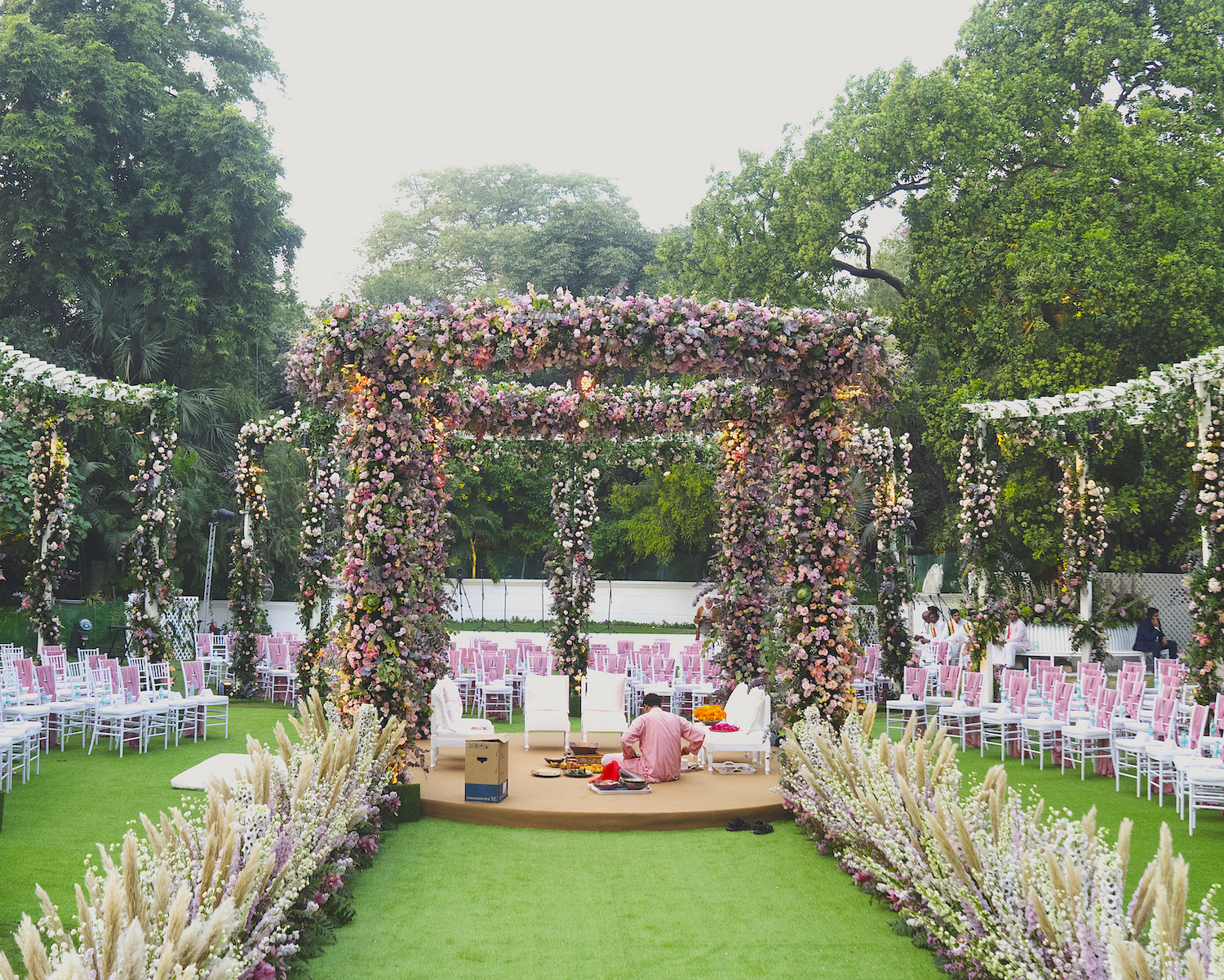 Outdoor Mandap decoration in an open area With Pastel Flowers plus white & pink guest seating chairs