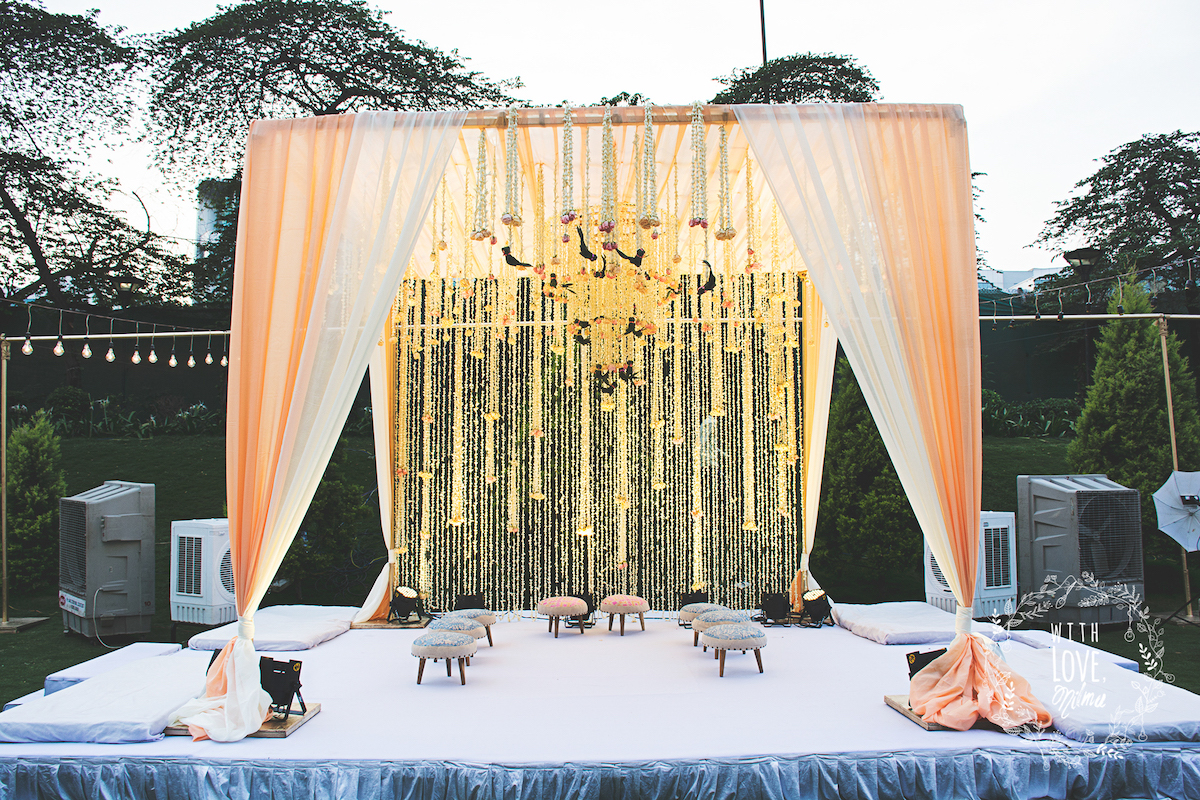 Simple mandap decoration with Curtain of Tuberoses and Floral Chandelier  with peach & white drapes