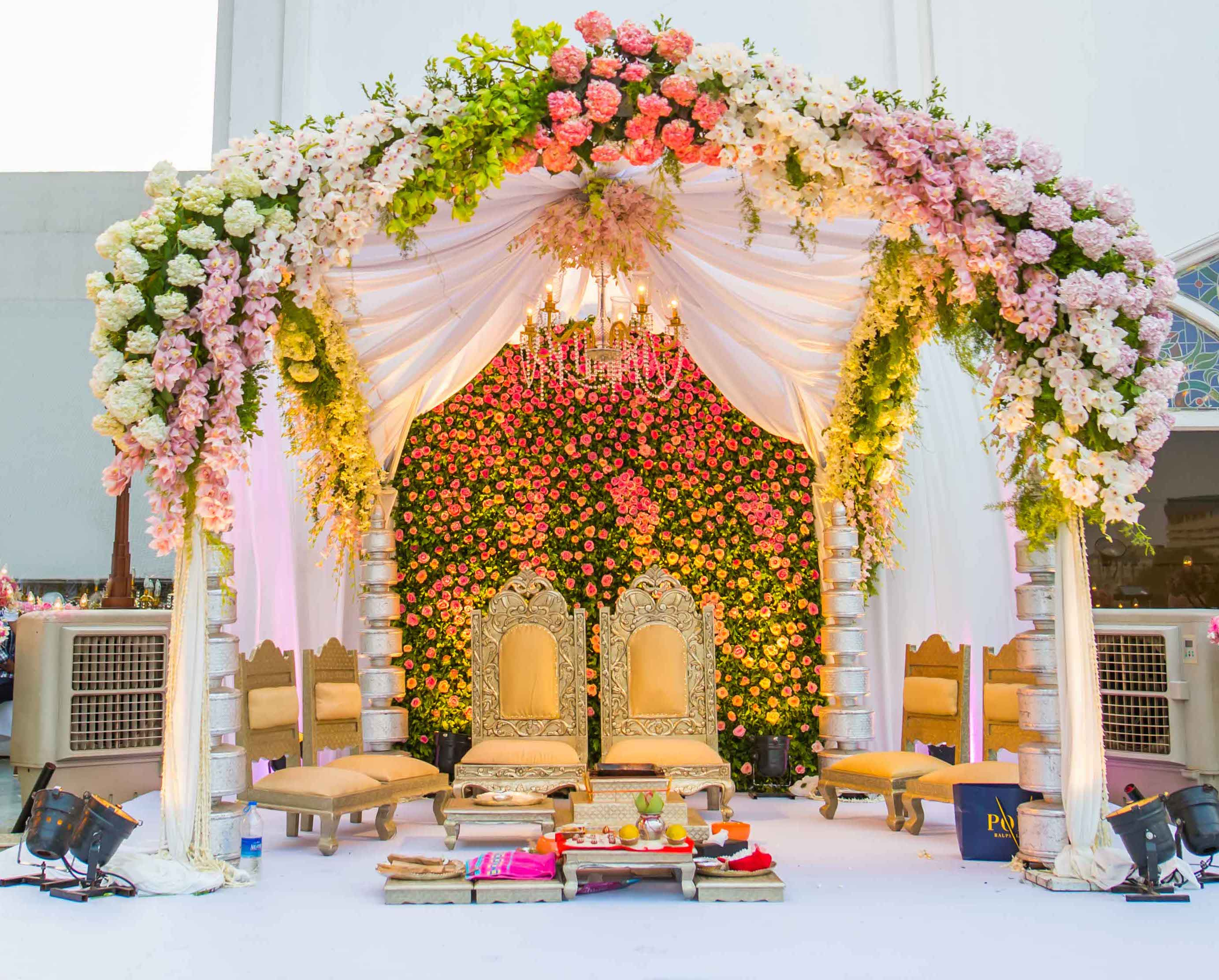 marriage mandap decoration with colourful flowers and golden mandap chairs