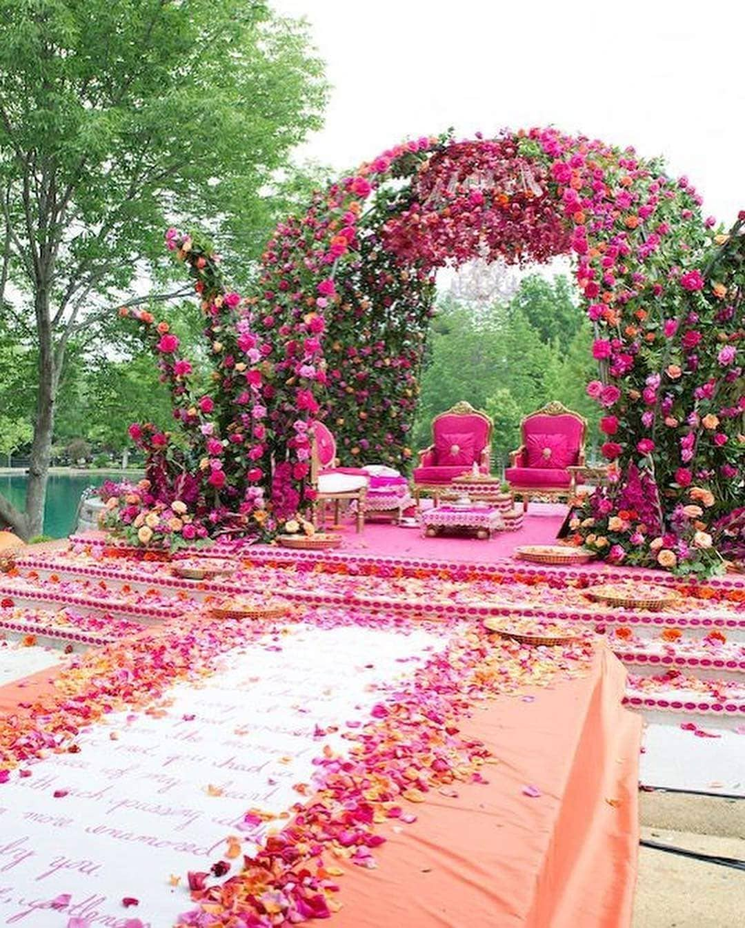 Wedding mandap decoration with pink flowers and wedding vows printed on the Aisle plus with pink and golden colour wedding mandap chairs
