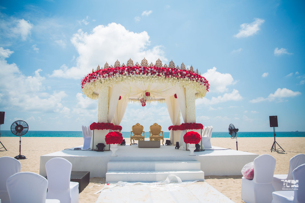 wedding mandap in white and cream colour with red flowers and gold mandap chairs