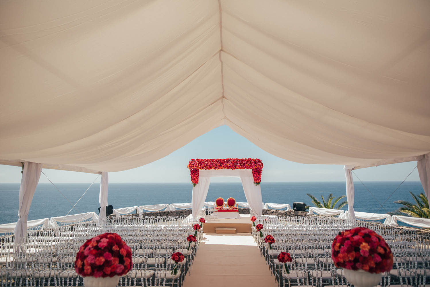 floral white mandap with red flowers in white wedding decor theme - white tent and white chairs for guest seating
