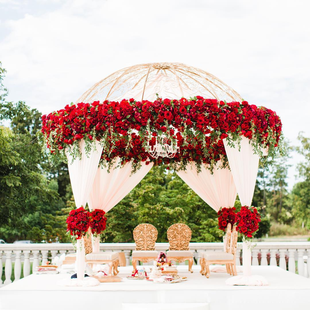 round wedding mandap decorated with Red Flowers & Greenery plus with white drapes