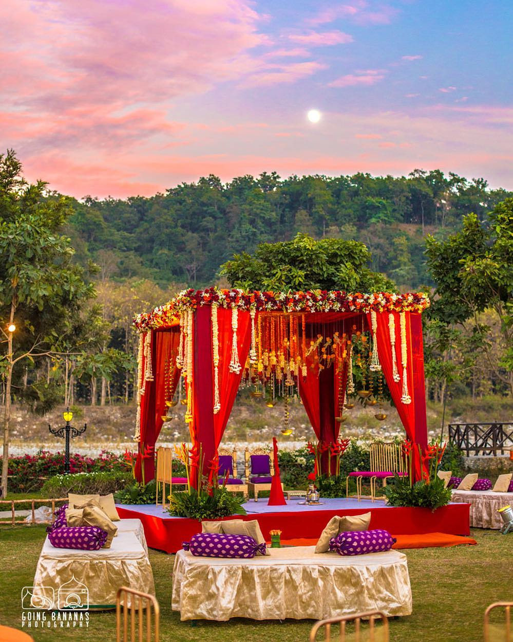 outdoor mandap design fully decorated with flowers and with red drapes