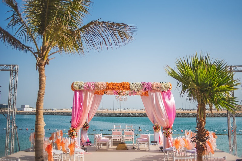 beach wedding mandap decorated with Pink, Peach, White & Orange flowers and with pink & white drapes