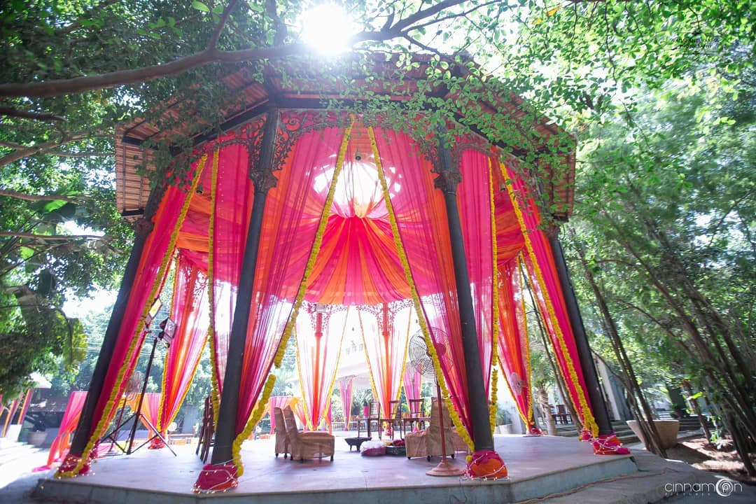 wedding mandap decoration image where mandap is decorated with Pink & Orange Drapes with Marigold Flowers