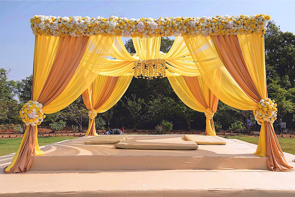 simple mandap decoration with yellow drapes and with yellow and white flowers