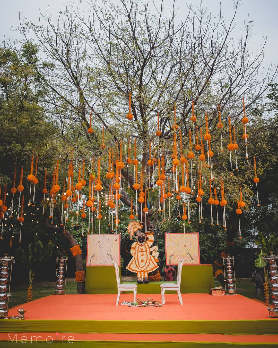 open wedding mandap decoration with Marigold Strings Hanging from a Tree's Branches and with white wedding mandap chairs
