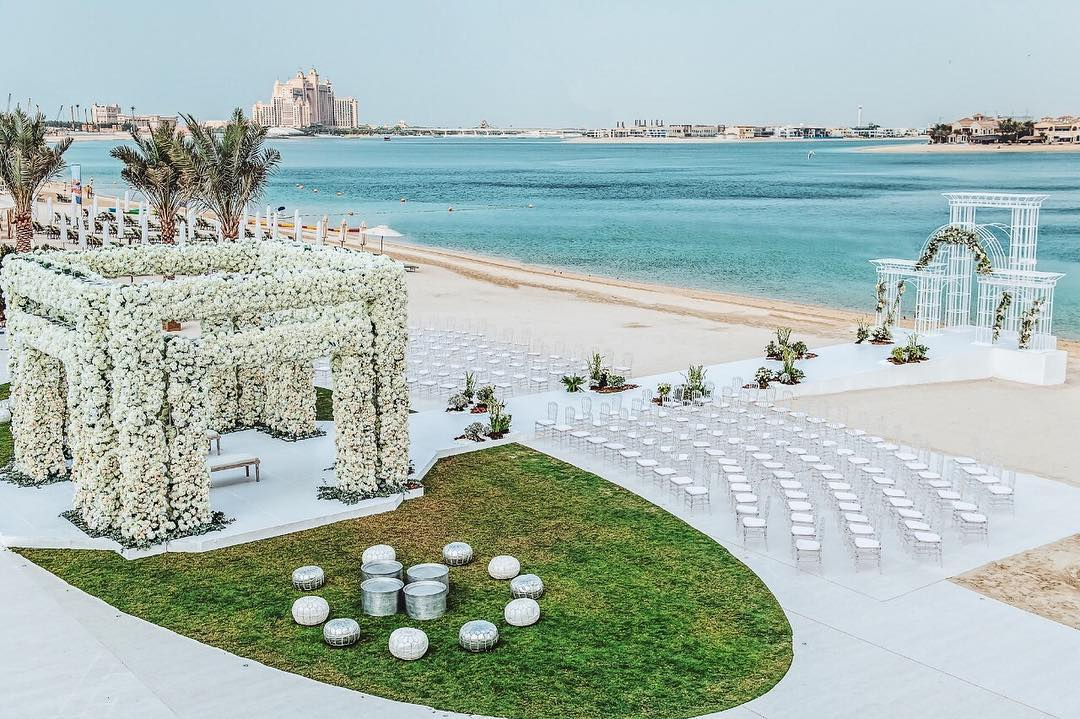 sea facing white floral mandap with white chairs