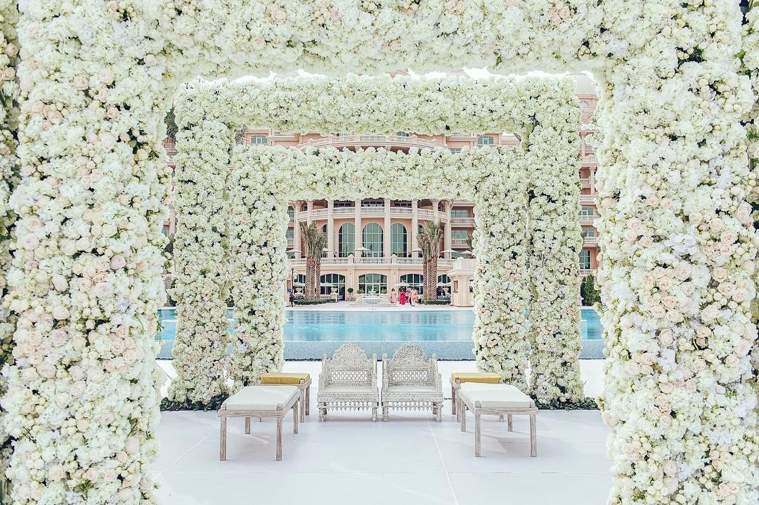white mandap with floral arches