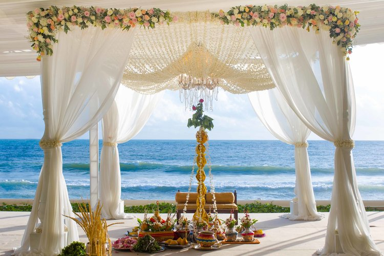 beach wedding white mandap with pink and yellow flowers and chandelier