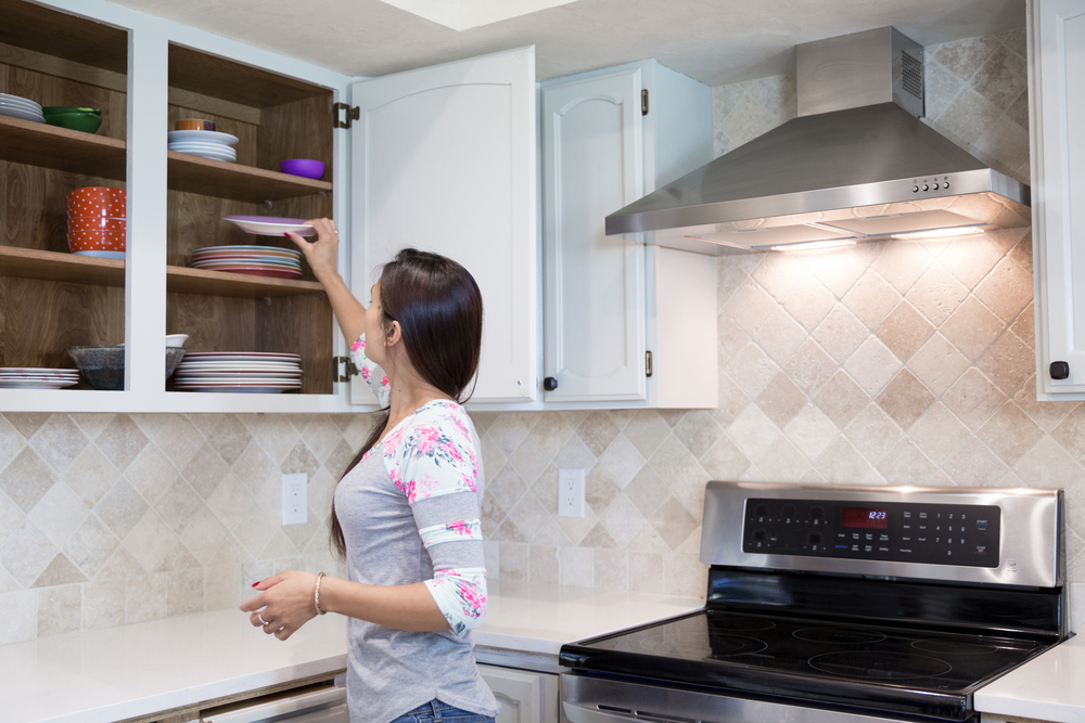 woman cleaning kitchen cabinet