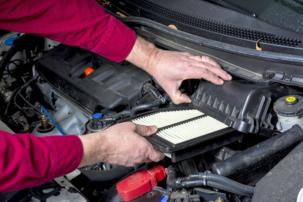man cleaning the air filter of his car