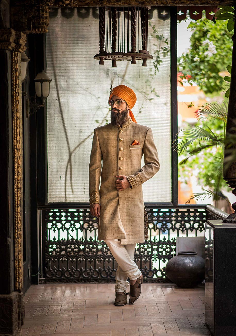 designer wedding turban for groom in orange perfectly matched with beige sherwani