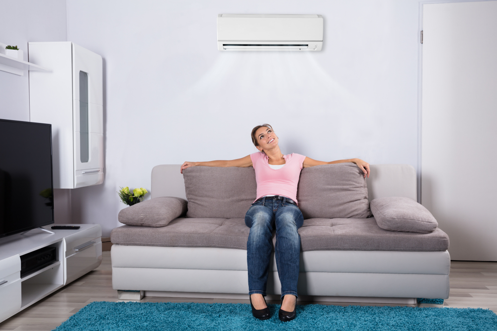 happy woman relaxing under AC