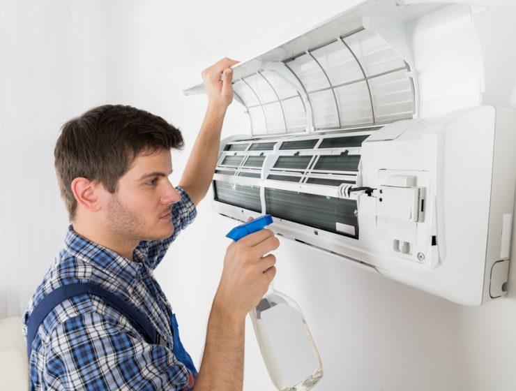man spraying in the AC