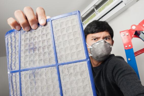man holding dirty air filter