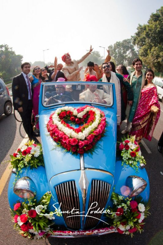 Groom entry in decorated vintage car at his wedding