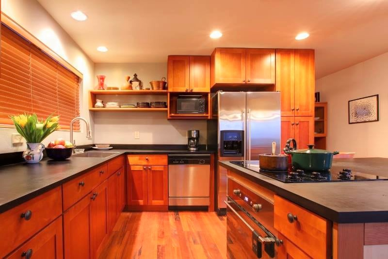 Open kitchen with wooden cabinets and island stove