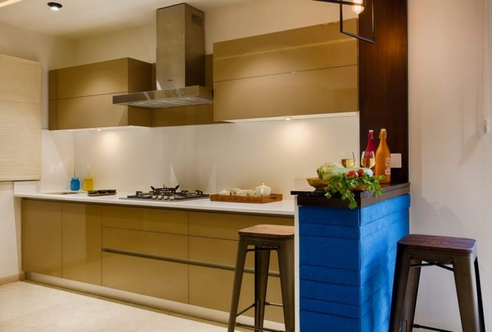 Beige modular kitchen with blue peninsula
