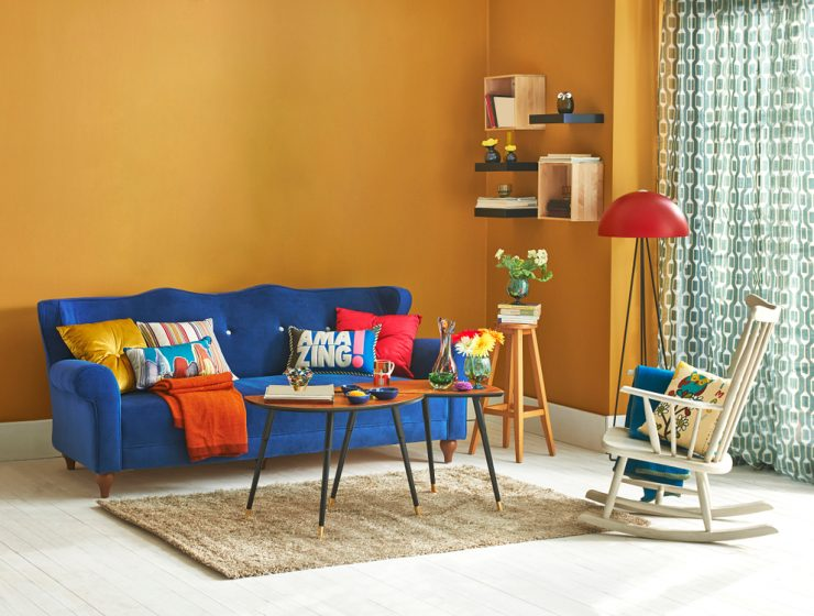 living room with yellow wall paint colour and blue sofa