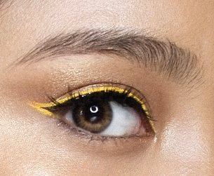 Yellow colored eyeliner on black eyeliner, with the yellow color curving inwards