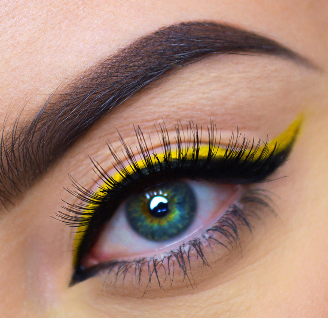 Bright yellow eyeliner on black eyeliner, with an extended wing