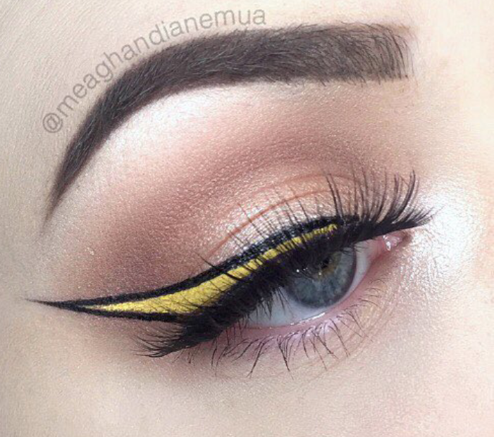 Yellow colored eyeliner within black winged eyeliner
