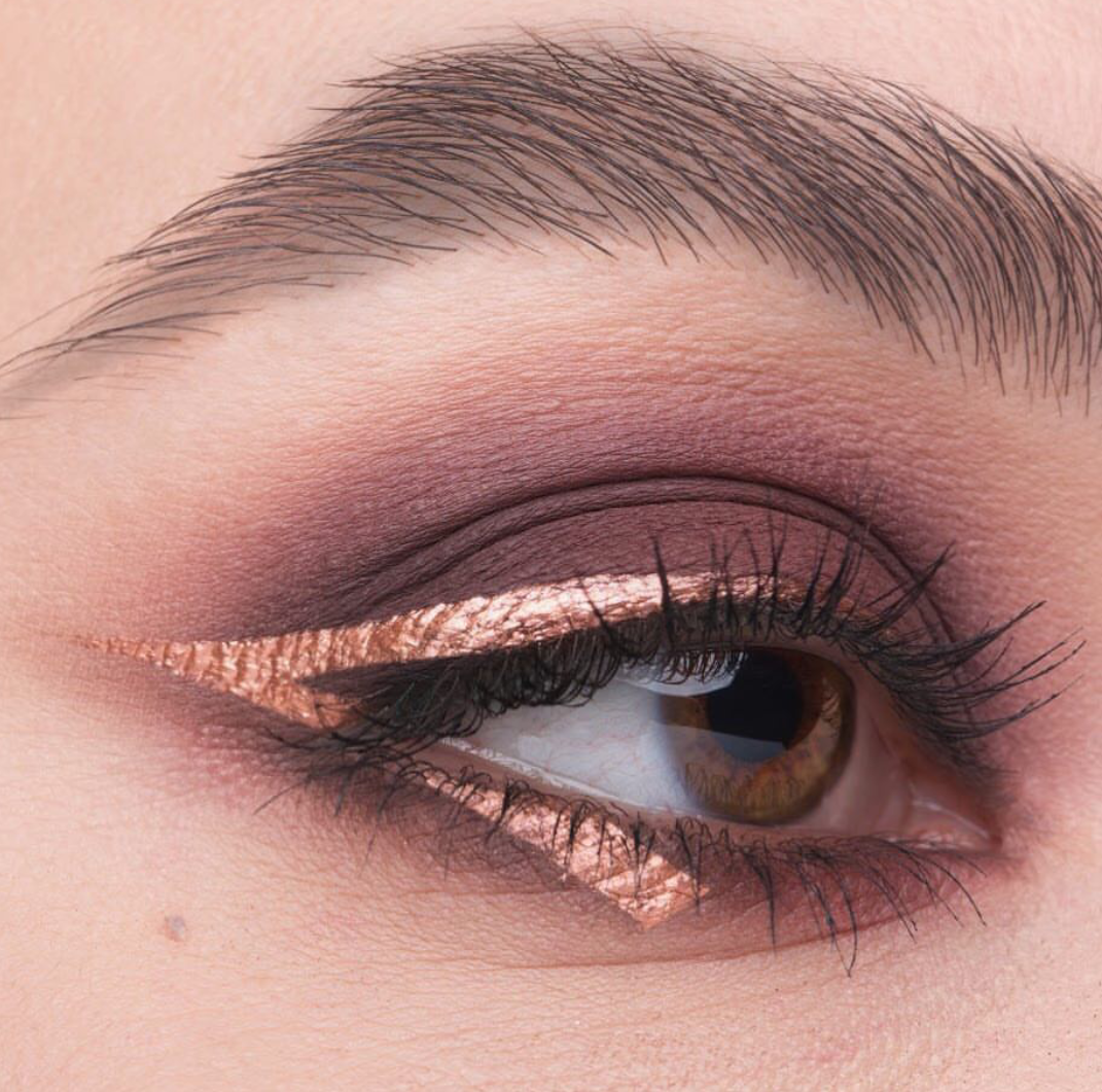 Gold colored matte eyeliner applied on just half the eye