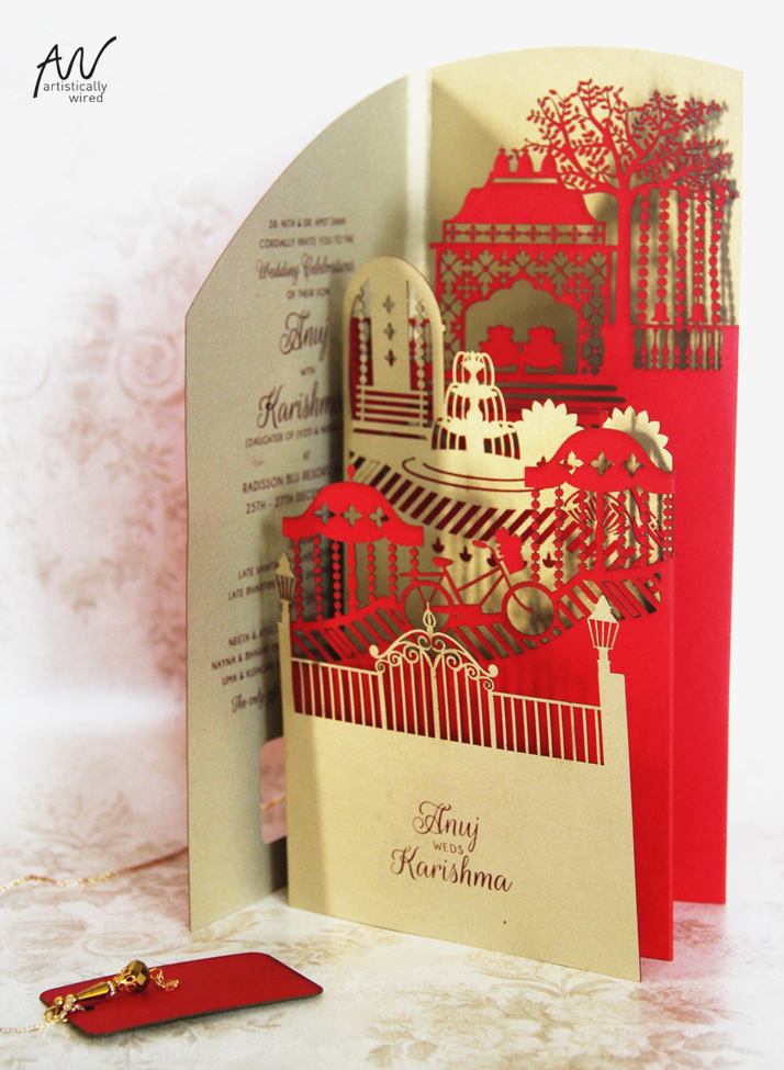 creative wedding invitation with lasercut elements of a fountain, the mandap, bicycle and a gate