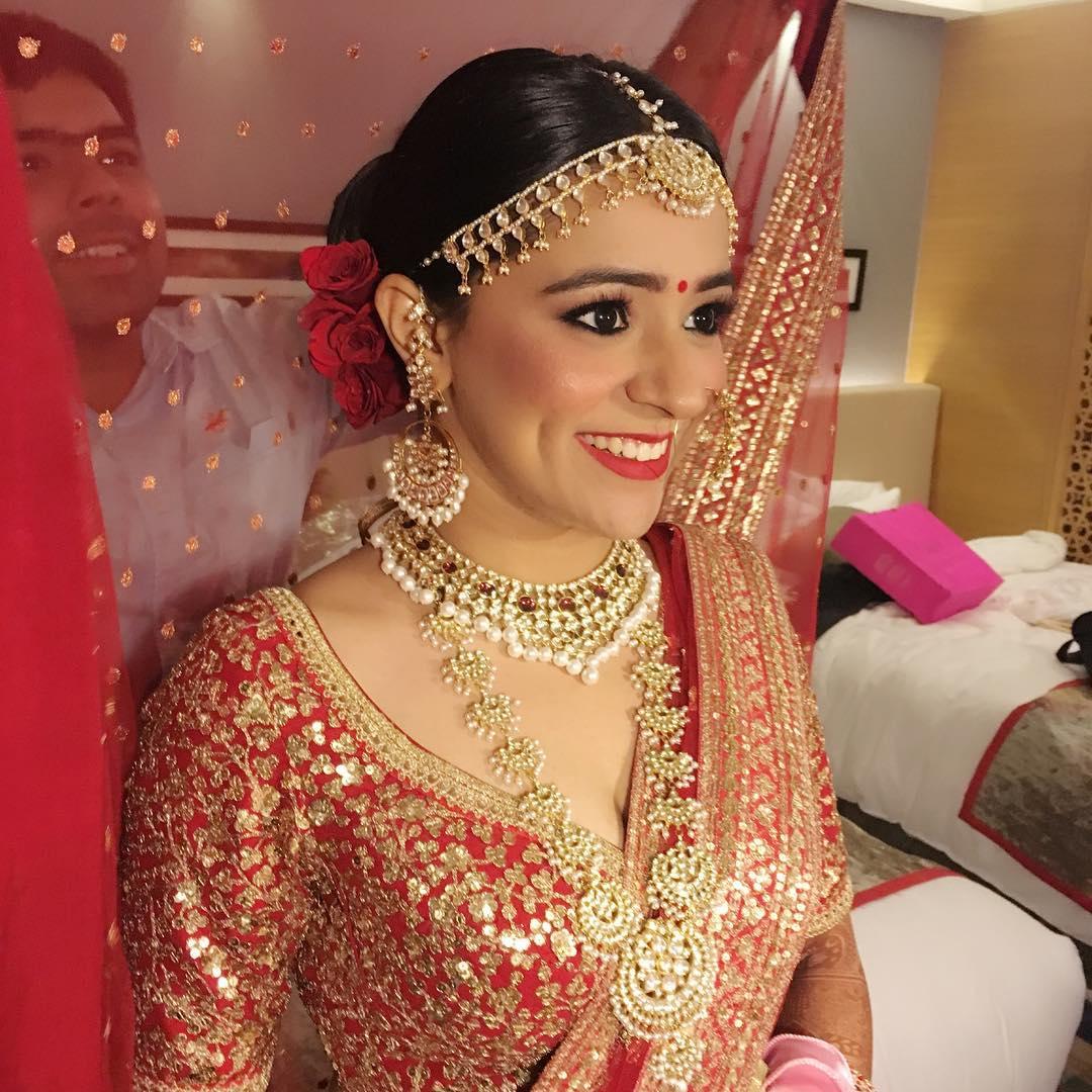 wedding makeup tips - makeup artist helping bride with her dupatta