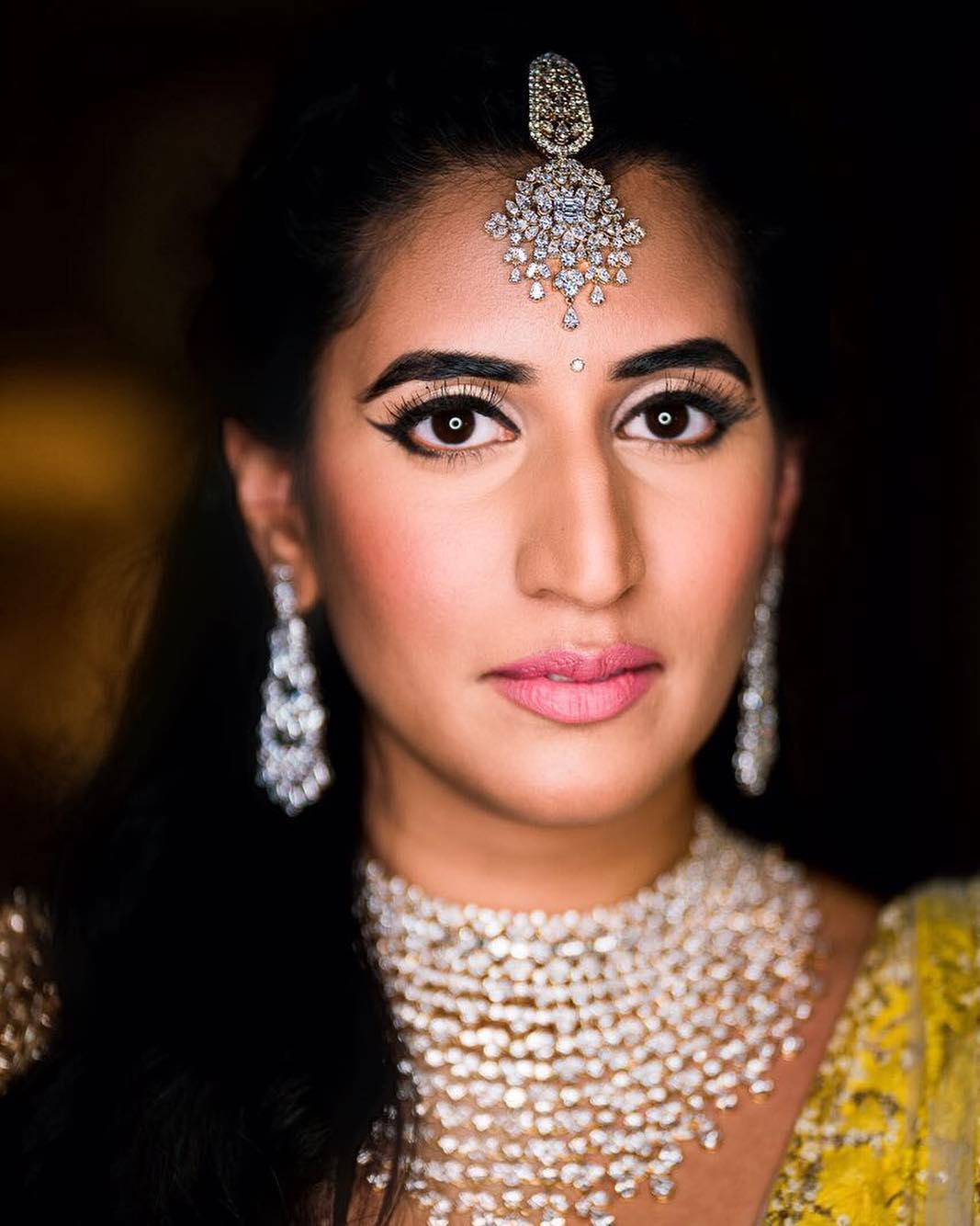 diamond maang tikka on Indian bride with soft makeup pink lips and dramatic eyeliner