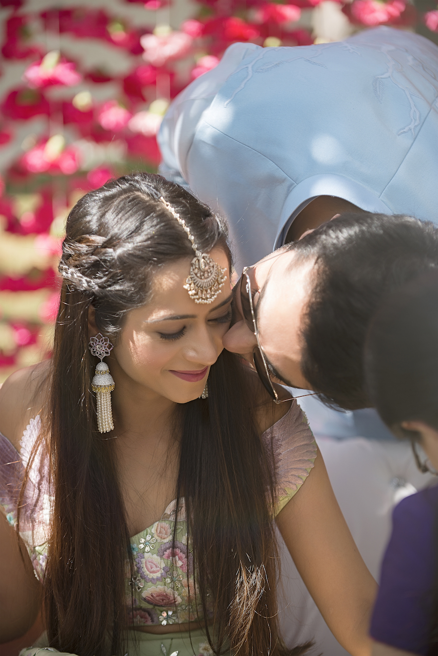 bride Kresha Bajaj on her Mehendi ceremony in silver and diamond maang tikka, customised floral chandelier earrings and middle parted hairstyle with twisty braids on the side