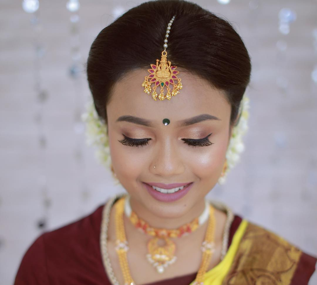 temple jewellery style unique gold maang tikka with God motif on South Indian bride