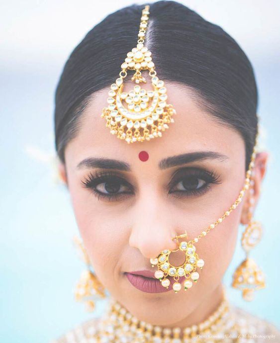 kundan maang tikka set in gold paired with round bridal nath on Indian bride with oval face
