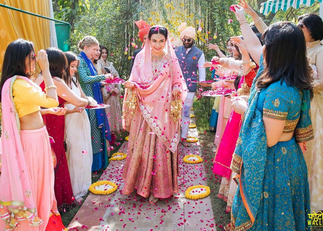 sweet indian bridal entrance with flower petals shower on bride