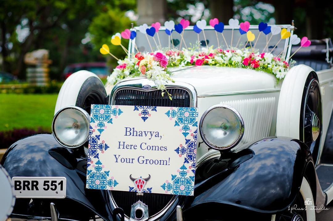 Decorated vintage car with sign for groom entry in Indian wedding