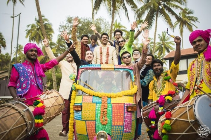 groom entry in Indian wedding - in a colourful auto with baraatis