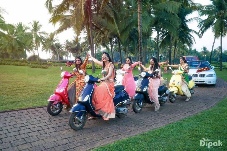 Bridesmaids entrance at Indian wedding with the bride - on scooters