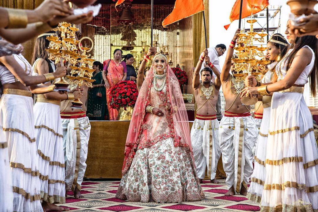 Bride entry in wedding with girls holding aarti lamps on both sides
