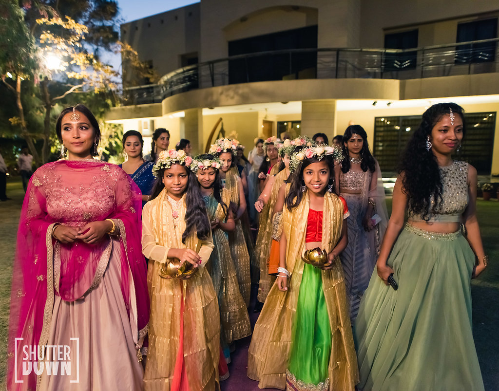Bride entry in marriage with nieces and little cousins holding diyas and wearing floral tiaras