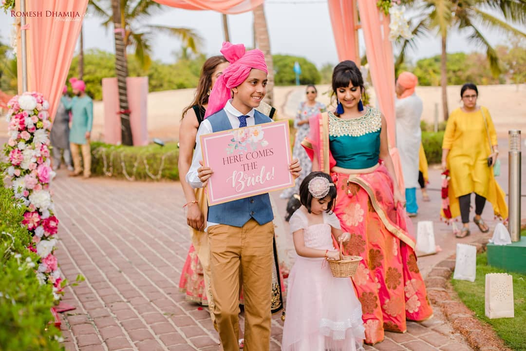 Indian Bridal entry idea with signs - your niece as flower girl and nephew holding up sign that says here comes the bride