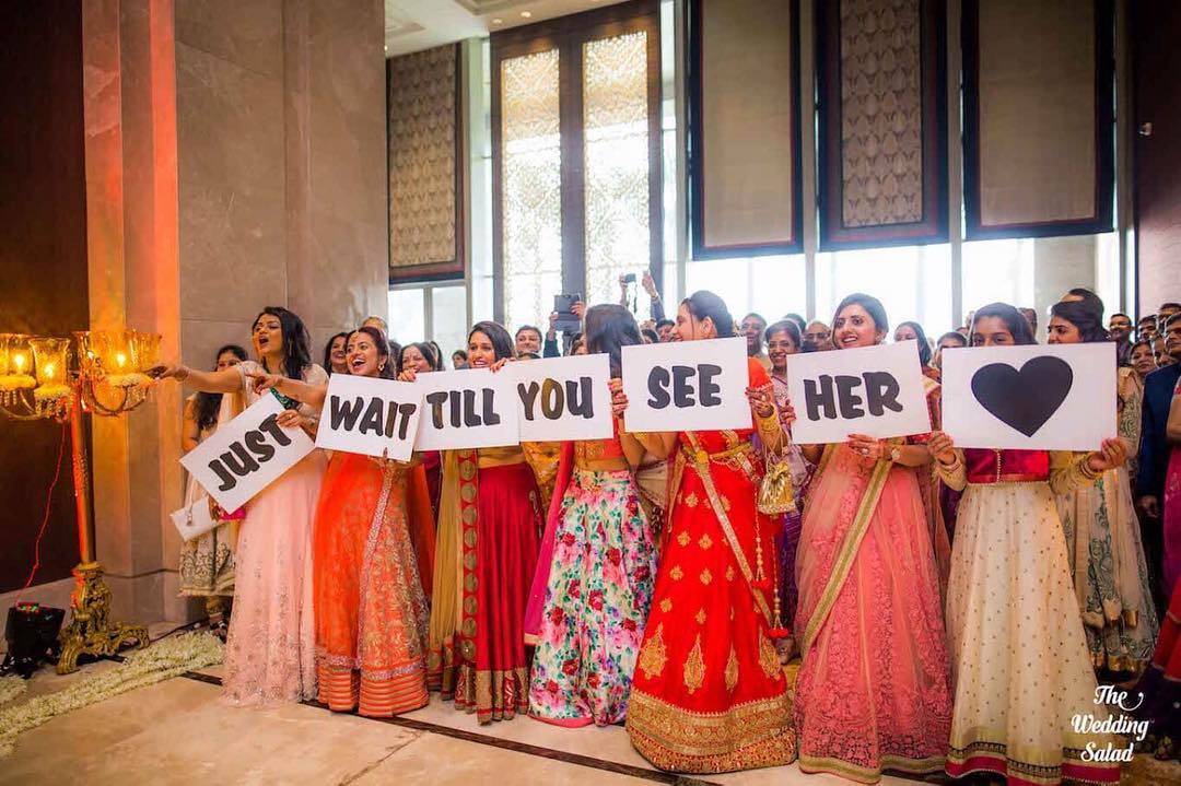 Bridal party entrance idea for Indian bride - your bridesmaids, friends and sisters holding up Just Wait Till You See Her
